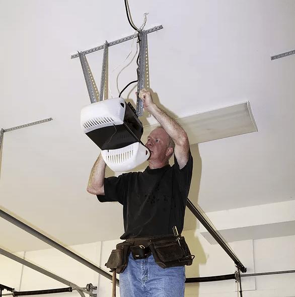 man repairing a garage door opener